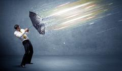 Business man defending light beams with umbrella concept Stock Photos
