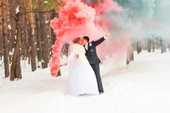Wedding couple with color smoke in the winter park. Colour bomb Stock Photos