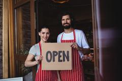 Couple holding open signboard at the entrance of bakery shop Stock Photos