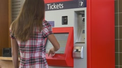 Woman buying ticket in ticketing machine Stock Footage