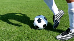 Footballer leading the ball on a football field, slow motion Stock Footage