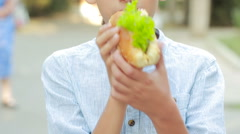 Boy outdoors eating a hamburger. child eating a sandwich in the street Stock Footage