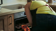 Female cook takes out tray with cupcakes from oven Stock Footage