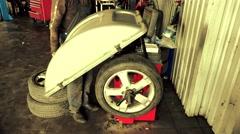 Mechanic balancing car wheel on an automated machine checking Stock Footage