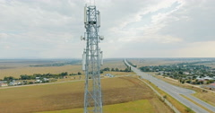 Aerial view on tower of cell phone antenna road with transportation and blue sky Stock Footage
