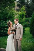 Young happy bride and groom on the background of greenery Stock Photos