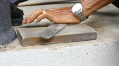 Close-up on a knife sharpener whetting a cleaver on the sidewalk Stock Footage