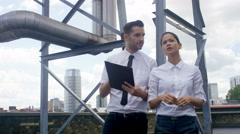 4K Business man & woman carrying out an inspection at urban industrial site Stock Footage