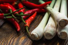 Mexican chili peppers with lemongrass scattered on the wooden table Stock Photos