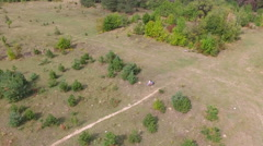Couple sitting in a clearing in the woods. Shooting with quadrocopters. Dron Stock Footage