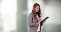 Attractive business woman intern using tablet in the office. Cute Woman in 20s Stock Footage