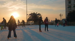 People skating on ice-rink at sunset, Greece Stock Footage