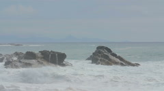 The foam of the waves covers the rocks in the sea Stock Footage