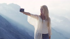 Attractive European girl with long blonde hair in jeans and white blouse is Stock Footage