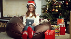 Pretty young girl in bright Christmas socks using pad and listen music Stock Footage