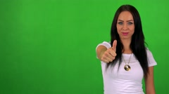 Young pretty woman shows thumb up on agreement - green screen - studio  Stock Footage