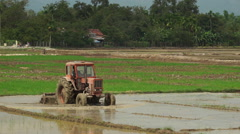 Tractor is leveling a ground with water slowly on the agricultural land in Stock Footage
