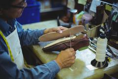 Shoemaker stitching shoe sole with needle in workshop Stock Photos