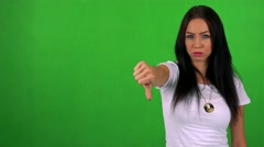 Young pretty woman disagrees (show thumb down) - green screen - studio Stock Footage
