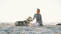 Young female playingwith siberian husky dog on the beach at sunrise, slow motion Stock Footage