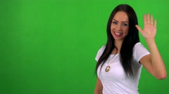 Young pretty woman waves with hand - green screen - studio  Stock Footage