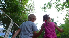 Girl with ears and pigtails and boy with white hair go by path along the fence Stock Footage