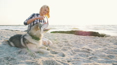 Young female putting sungglasses on siberian husky dog on the beach,slow motion Stock Footage