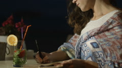Closeup of happy and inspired pretty woman writing in diary with smile on face Stock Footage