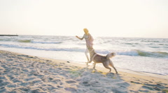Young female running with siberian husky dog on the beach at sunrise,slow motion Stock Footage