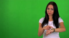 Young pretty woman points on watch (show time) - green screen - studio  Stock Footage