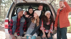 Friends sit talking in the open back of a car before a hike Stock Footage