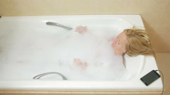 Beautiful woman taking a bath and listening to music on headphones. cell phone Stock Footage