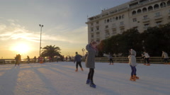 Children and young people on outdoor skating rink at sunset Stock Footage