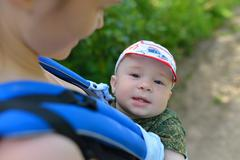 Mother and beutiful baby walking outdoors, happy boy smiling  looking to the Stock Photos