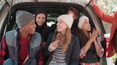 Friends sit talking at the open back of a car, close up Stock Footage