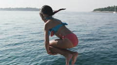 Child little girl is jumping into the sea from a pier. Slow motion Stock Footage