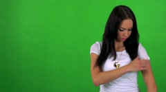 Young pretty woman adjusts hair and smiles to camera- green screen - studio  Stock Footage