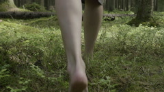 Girl walks barefoot in the woods in a cloak Stock Footage