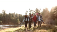 Multi generation family walking towards camera near lake Stock Footage