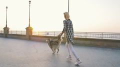 Young female tunning with siberian husky dog on sea front at sunrise, slowmo Stock Footage