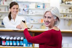 Portrait of pharmacist giving medicine to customer in pharmacy Stock Photos