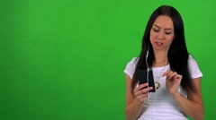 Young pretty woman listens music with earphone on smartphone - green screen  Stock Footage