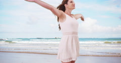 Young happy woman standing at the beach feeling the ocean breeze. Brunette woman Stock Footage