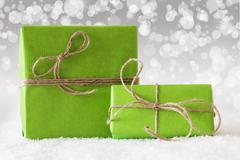 Two Green Gifts On Snow, White Bokeh Effect Stock Photos