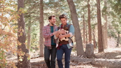 Male parents in forest with baby in sling pass out of shot Stock Footage