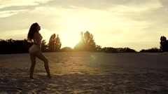 Sexy girl doing forward walkover on the sand at sunset Stock Footage