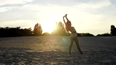 Sexy girl doing backward walkover on the sand at sunset Stock Footage