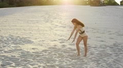 Dancer girl with a beautiful body gets up on his hands and falls on the sand Stock Footage
