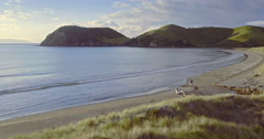 Aerial of man walking on an empty beach in the Coromandel, New Zealand Stock Footage