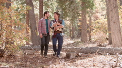 Male couple in forest with baby in sling walk towards camera Stock Footage